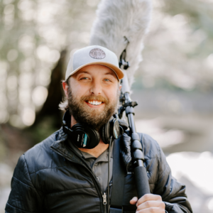 lucas cooper smiling at the camera holding a boom mic over his shoulder