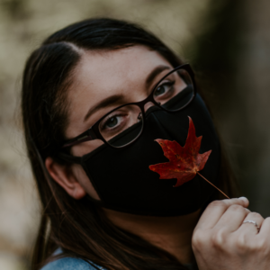 Jess Gutman holding leaf in front of her face with a face mask on