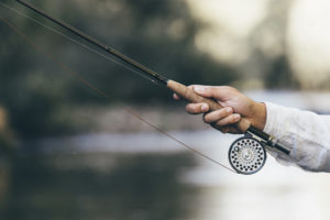 Fly fishing rod in fisherman hand.