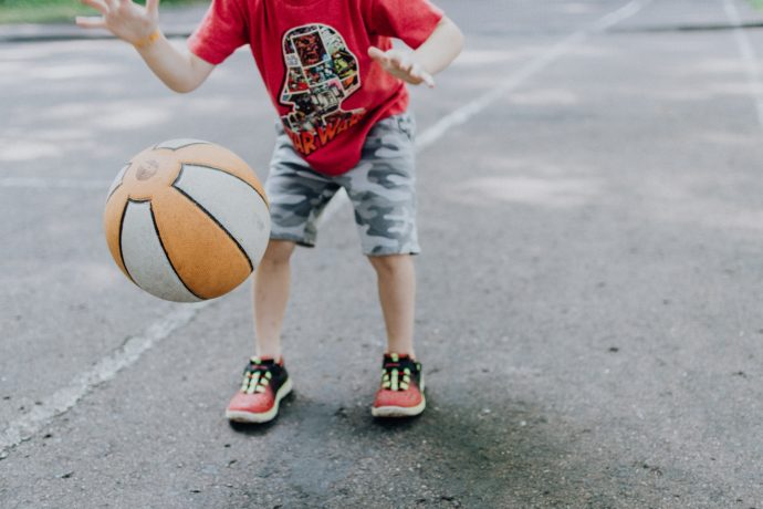 young child bouncing a basketball