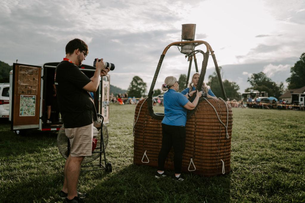 Eli Heaton pointing a camera at a woman setting up a hot air balloon